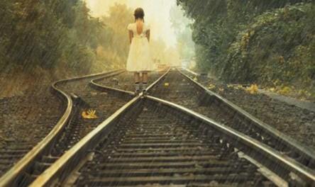 alone little girl walking in rain on railway